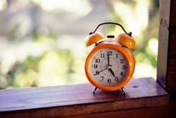 High quality image. Photograph of an orange antique clock. Image to use as a background.