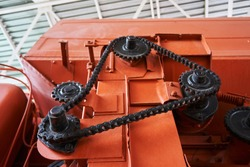 high-quality metal gears and chains on an old tractor of bright orange color in the museum of agricultural equipment