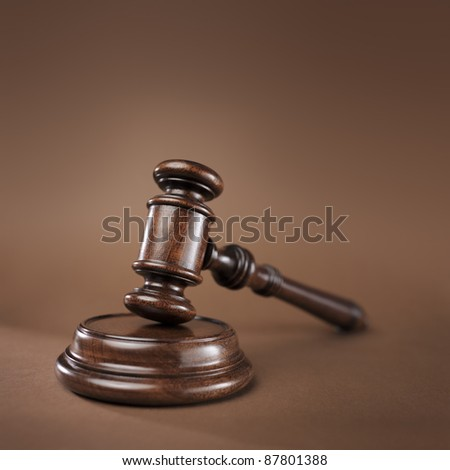 High quality wooden gavel and block on brown background. Short depth-of-field.