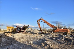High Reach Excavator machines for demolition of tall building. Machine with hydraulic shears for demolish. Mobile Stone crusher for crushing concrete. Recycling and disposal of construction waste