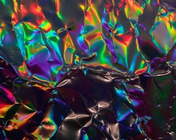 high res full frame macro photo of abstract crumpled iridescent holographic foil background with light leaks. holo color wrinkled material. cool glitter surface with shiny rainbow color blocking feel.