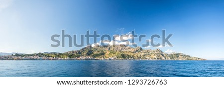 High res panoramic shot of the beautiful Giardini Naxos bay with mountains in the background near Taormina, on Sicily, Italy