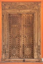 High-resolution ancient wood carved door. Old Indian double door with knocker handles and chain. Traditional vintage wooden door ornaments. Antique door hi-res texture