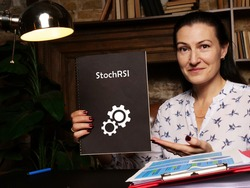 High resolution business Woman holding black notepad with written text StochRSI Stochastic RSI - closeup shot.