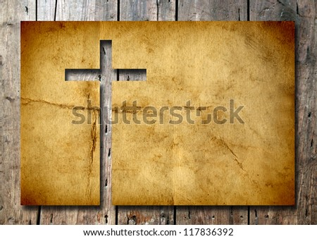 High resolution christian cross cut in an old grungy or vintage paper, over a wood background, ideal for religion, Christian, grunge or conceptual designs