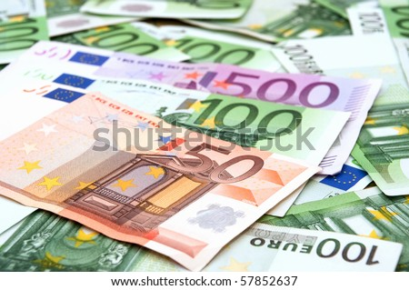 High resolution, detailed image of pile of 100 Euro banknotes scattered around.