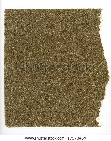 High resolution image of torn piece of coarse sandpaper on a white background.