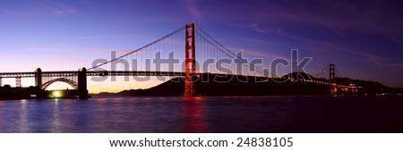 High resolution stitched image of glowing Golden Gate bridge and Fort Point at sunset. First stars can be seen in the sky.