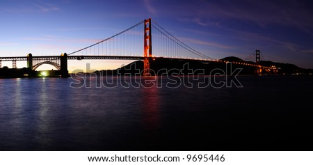 High resolution stitched image of glowing Golden Gate bridge and Fort Point at sunset. First stars can be seen in the sky. - stock photo