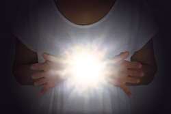 High Resonance White Light Healing Energy Phenomenon  - female in white tunic with hands apart at chest level with a bright shining white orb light between