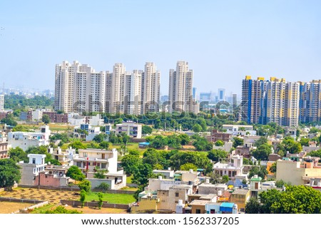 High Rise apartment in Delhi NCR region. Standalone houses and some grass field can also be seen. Urbanization is in full focus