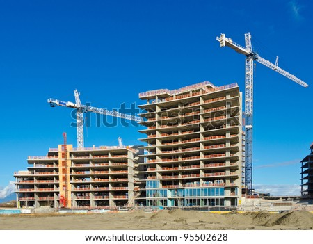 High-rise building construction site with cranes against blue sky