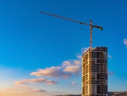 High-rise building, crane, blue sky, white clouds in the light of the setting sun
