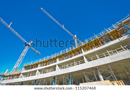 High-rise building under construction. The site with cranes against blue sky. Vancouver, Canada.