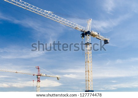 High-rise building under construction. The site with cranes against blue sky with white clouds