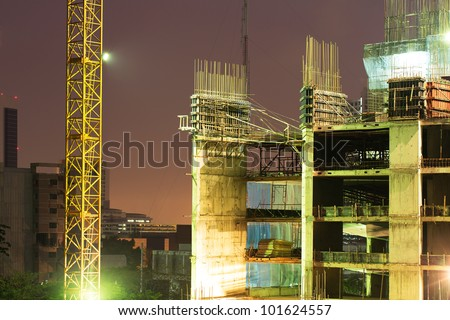 High rise concrete building construction with a yellow crane