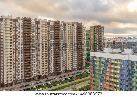 High-rise multi-storied residential buildings with balconies and windows against cloudy sky at sunset. Apartment houses and yard with car parking. Housing construction or sale of apartments concept
