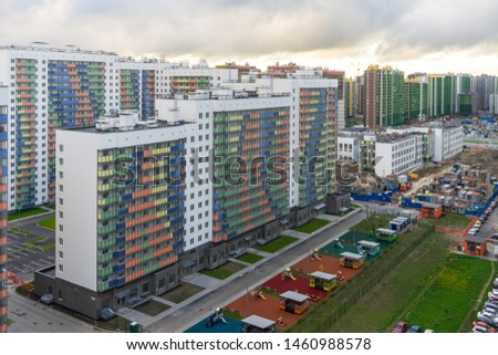 High-rise multi-storied residential buildings with balconies and windows against cloudy sky at sunset. New apartment houses and yard. Housing construction or sale of apartments concept