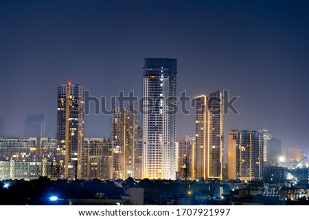 High rise multi story skyscrapers lit up at night with small houses in the foreground at night in gurgaon delhi. Shows the rapid pace of development of the real estate sector with property, offices