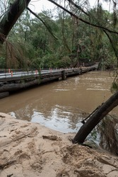 high river waters and a wooden bridge in australia