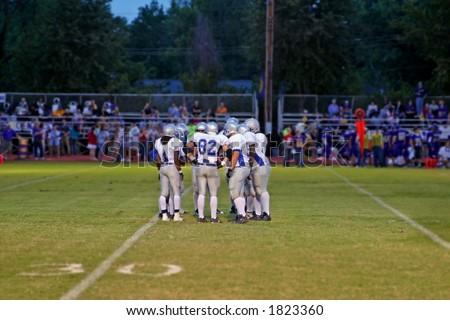 High School football team huddles around the QB