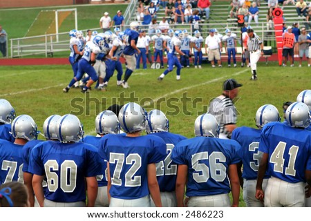 High school football team on the sidelines watching a game in progress.