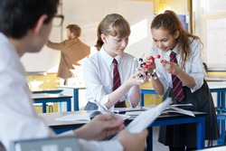 High school girls assembling a molecule model in a science class with a classmate in the foreground.