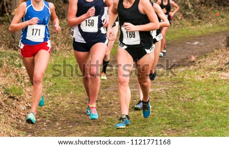 High school girls on a dirt path in the woods during a cross country invitatiional race in late autumn. #1121771168