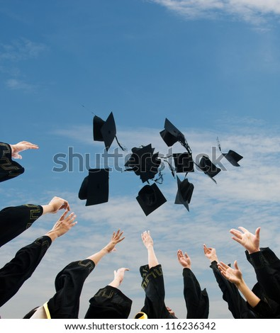 high school graduates tossing up hats over blue sky. - stock photo