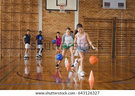 High school kids practicing football using cones for dribbling drill in the court