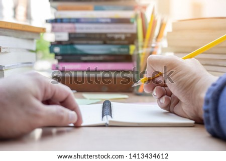 high school or university student holding pencil writing on paper answer sheet.sitting on lecture chair taking final exam attending in examination room or classroom.student in uniform