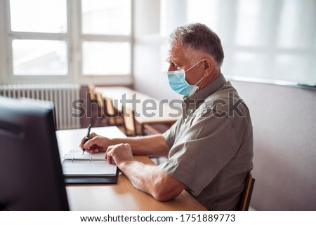 High school professor in classroom with face mask. Covid-19 concept
