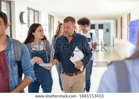 High school student asking doubt to professor. Mature man professor answering to girl in university campus. High school lecturer talking to schoolgirl at the end of the lesson while walking in hallway