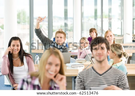 High school student raising hands in classroom