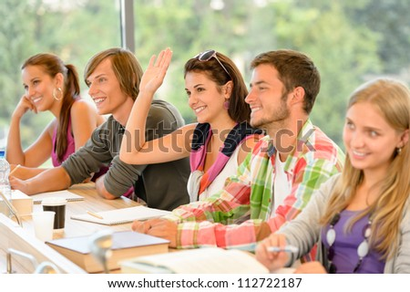 High-school student raising her hand in class lesson teenagers study