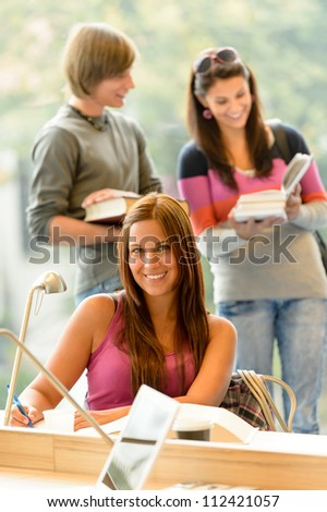 High-school student taking notes in library study smiling campus education
