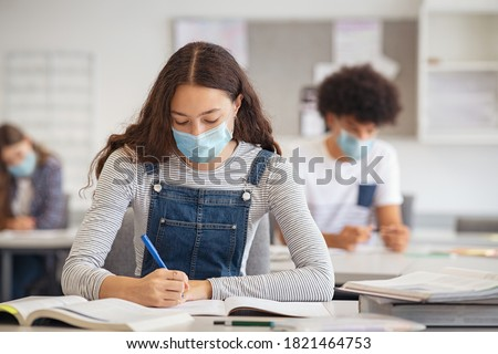 Photo of  High school student taking notes while wearing face mask due to coronavirus emergency. Young woman sitting in class with their classmates and wearing surgical mask due to Covid-19 pandemic.
