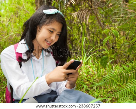 High School student using mobile phone for social media interaction in the park