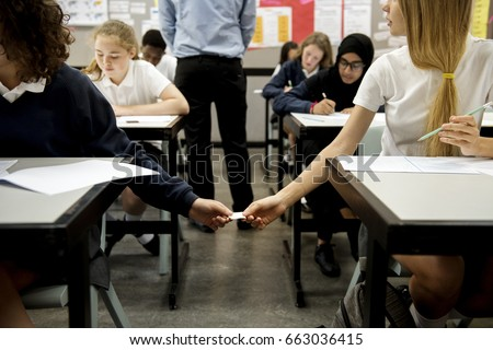 High school students cheating passing note on examination