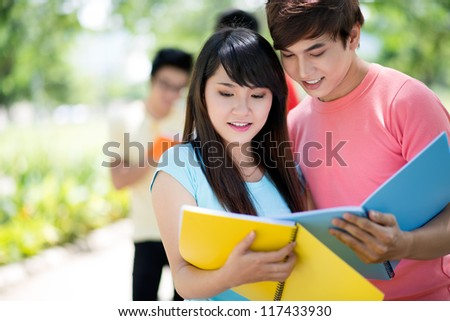 High-school students comparing homework before the lesson