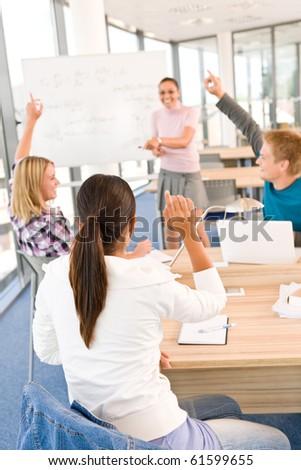 High school students raising hands, in classroom with professor
