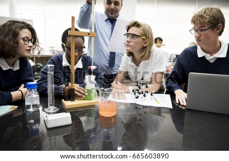 High school students studying chemistry laboratory experiment class