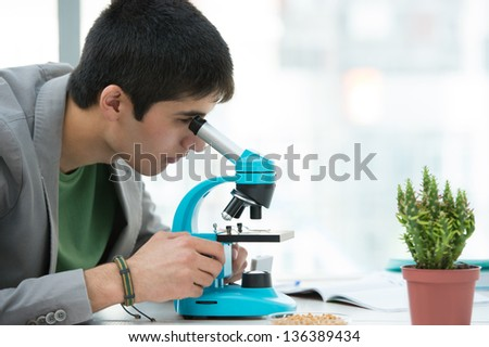 High School students. Young handsome male student looking through microscope biological sample in science classroom