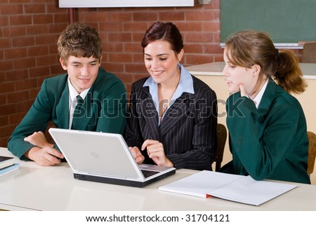 high school teacher and students looking at computer