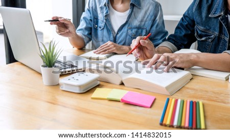 High school tutor or college student group sitting at desk in library studying and reading, doing homework and lesson practice preparing exam to entrance, education, teaching, learning concept. Stockfoto ©