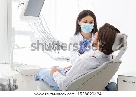 High service, care concept. Dentist woman making check up for patient in modern dental office, empty space Foto stock ©