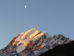 High sharp mountain with snow and glaciers in evening setting sun. The sky turns dark with half moon shining abobe the mountain. Mount Cook, highest mountain of New Zealand.
