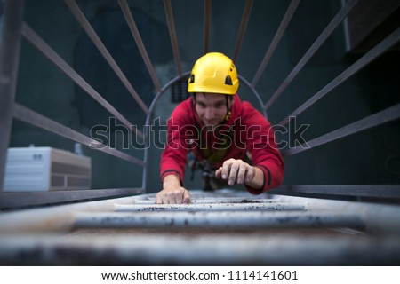High shoot picture of male hand industry rope access worker wearing full safety harness, helmet climbing safety ladder with blurry face back ground at construction site in Sydney city, Australia