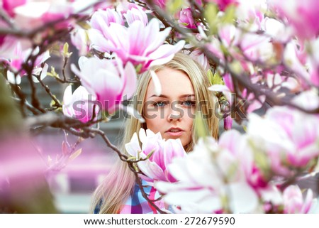 High society blond lady in pink blooming flowers looking at camera outdoors