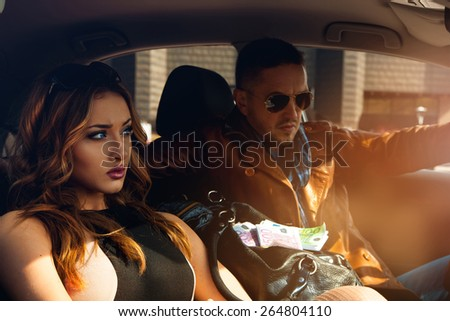 High society sexy couple in car looking away. Inside photo